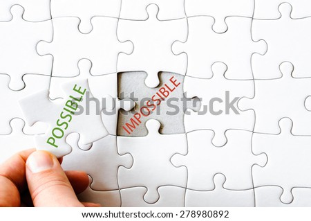 Hand with missing jigsaw puzzle piece. Word POSSIBLE, covering  the text IMPOSSIBLE. Business concept image for completing the final puzzle piece.