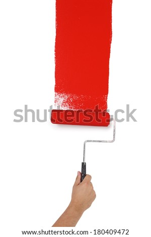 Hand with paint roller painting red on wall, cut out, isolated on white background - stock photo