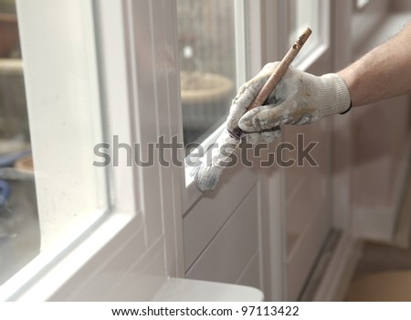 Hand with paintbrush painting a door white - stock photo