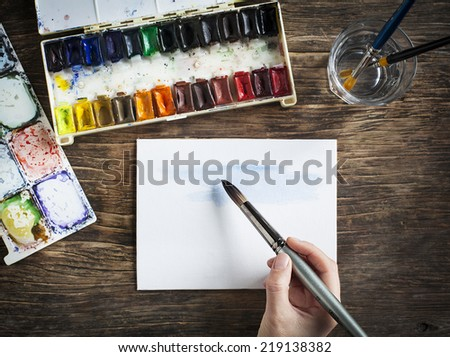 Hand with paintbrush. Painting with watercolor. Selective focus - stock photo