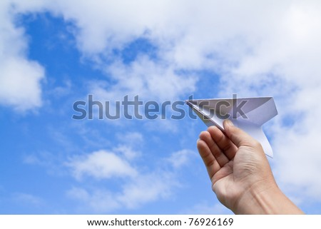 hand with paper plane against blue sky - stock photo