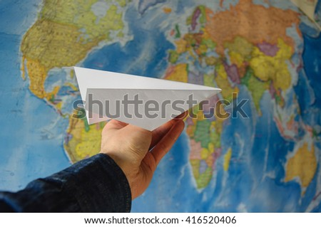 hand with paper plane against World map - stock photo