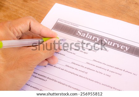 Hand with pen choosing salary survey from on the table - stock photo