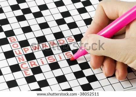 hand with pen crossword puzzles about the crisis