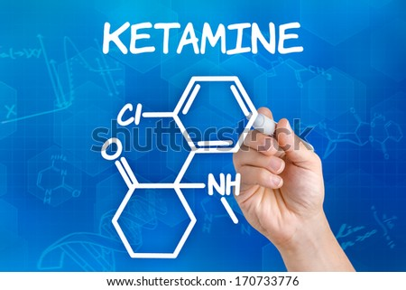 Hand with pen drawing the chemical formula of ketamine - stock photo
