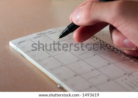 hand with pen on datebook - stock photo