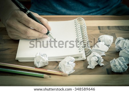 Hand with pen on empty note book with crumpled papers around - stock photo