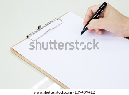 Hand with pen over paper - stock photo