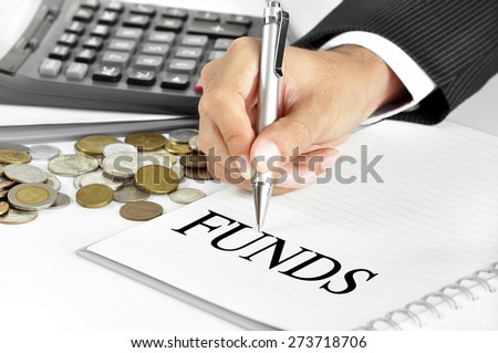 Hand with pen pointing to FUNDS word on the paper - financial and investment concept - stock photo