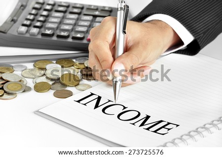 Hand with pen pointing to INCOME word on the paper - financial and investment concept - stock photo