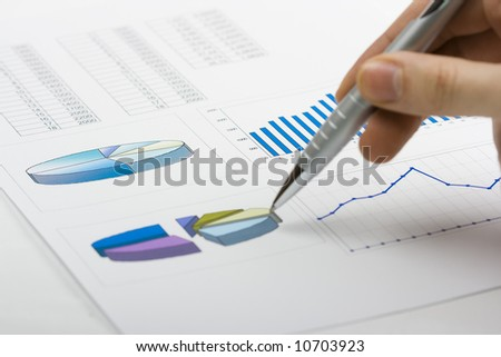 hand with pen showing report with diagrams - stock photo