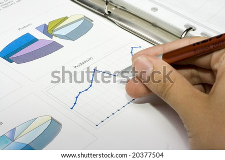hand with pen showing report with diagrams