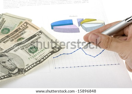 hand with pen showing report with diagrams and U.S. dollars - stock photo
