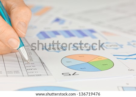 Hand with Pen working on Spreadsheet and Graphs  - stock photo