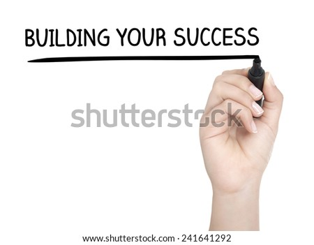 Hand with pen writing BUILDING YOUR SUCCESS on whiteboard - stock photo