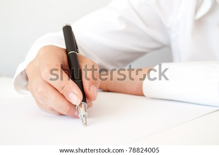 hand with pen writing on the white paper - stock photo