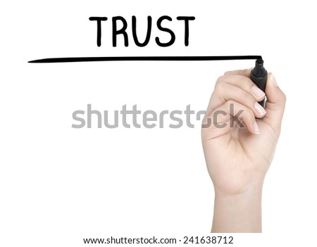 Hand with pen writing TRUST on whiteboard - stock photo