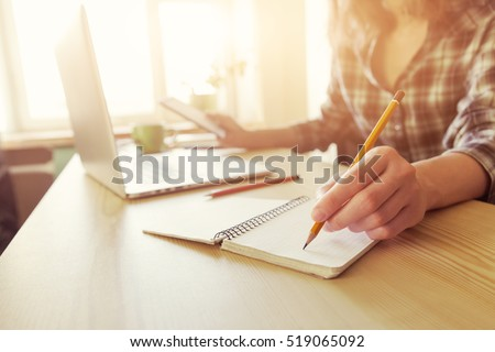hand with pencil and notebook at workplace
