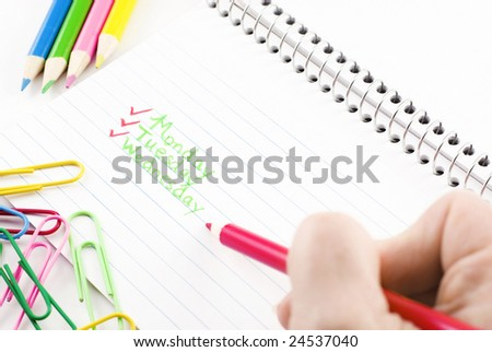 Hand with pencil checking off days of week, index card with paperclips - stock photo