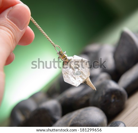 Hand with pendulum, tool for dowsing. - stock photo