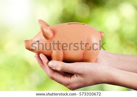 hand with piggy bank savings on natural background
