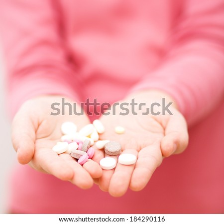 Hand with pills medicine tablets - stock photo