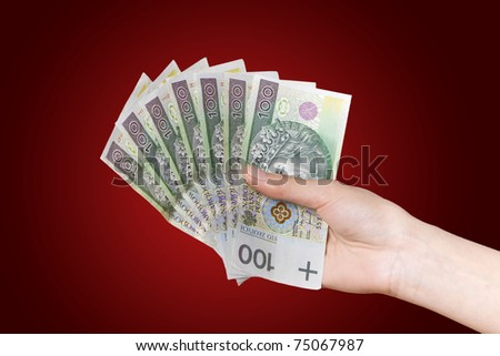 Hand with polish money on red background - stock photo