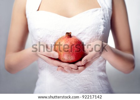 hand with pomegranate on background - stock photo