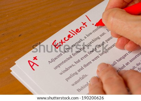 Hand with Red Pen Grading Papers with Excellent - Success concept in education industry  - stock photo