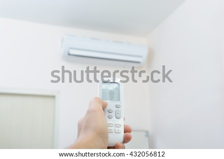 Hand with remote control directed on the conditioner - stock photo