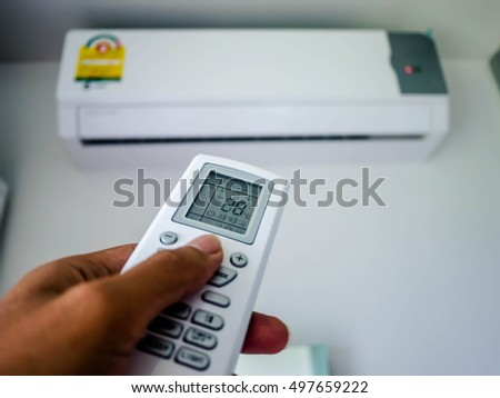 Hand with remote control directed on the conditioner and Reduce Air conditioner to reduce global warming