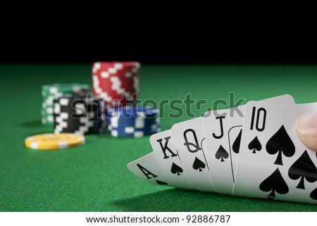 hand with royal flush,chips - stock photo