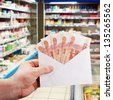 hand with rubles in the envelope against the supermarket shelves - stock photo