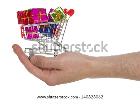 Hand with shopping cart full of gifts. Isolated on white background