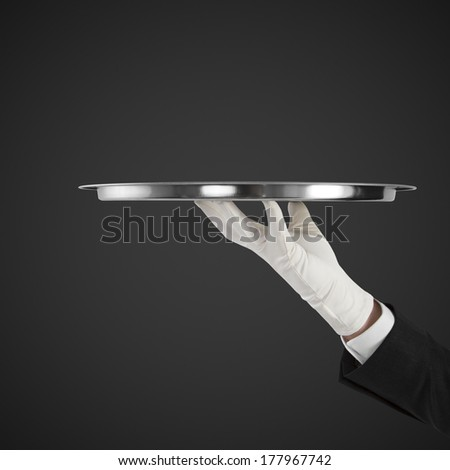 hand with silver plate isolated on a black background - stock photo