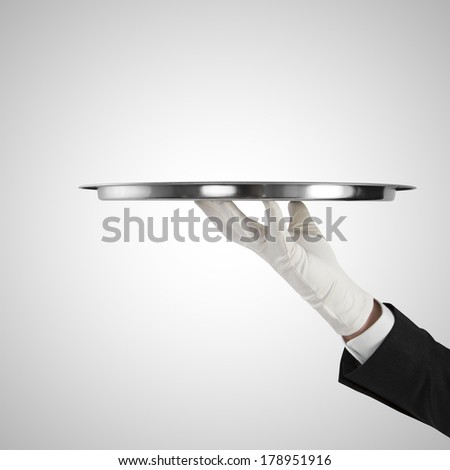 hand with silver plate isolated on a gray background