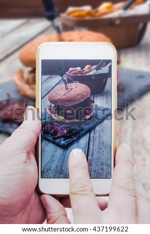 Hand with smart phone, taking picture of  food, bacon cheeseburger with potato cuts on vintage wood  table for sharing online