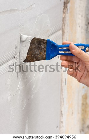 hand with spatula plastering a wall, closeup - stock photo