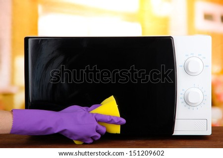 Hand with sponge cleaning  microwave oven, on bright background - stock photo