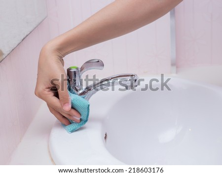 Hand with sponge cleaning white sink and faucet - stock photo