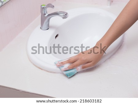 Hand with sponge cleaning white sink and faucet