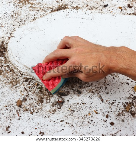 Hand with sponge cleans a very dirty surface - stock photo