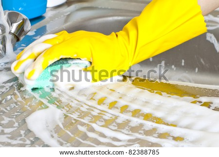 Hand with sponge washes sink - stock photo