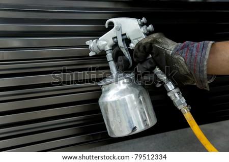 Hand with spray paint gun - stock photo