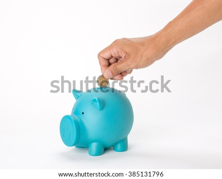 Hand with thai coin over a blue piggy bank on white background