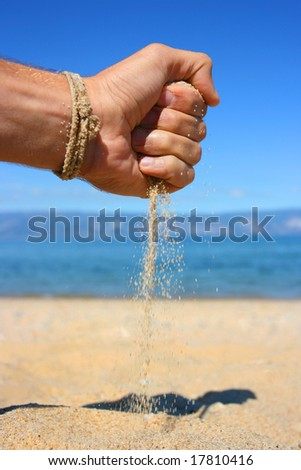 Hand with the sand at the beach - stock photo