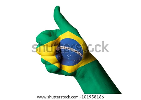 Hand with thumb up gesture in colored brazil national flag as symbol of excellence, achievement, good, - for tourism and touristic advertising, positive political, social management of country - stock photo