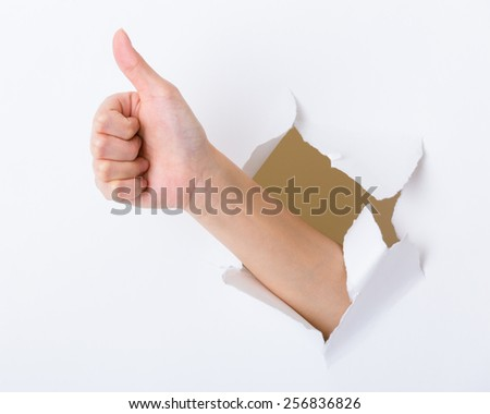 Hand with thumb up through a hole in paper - stock photo