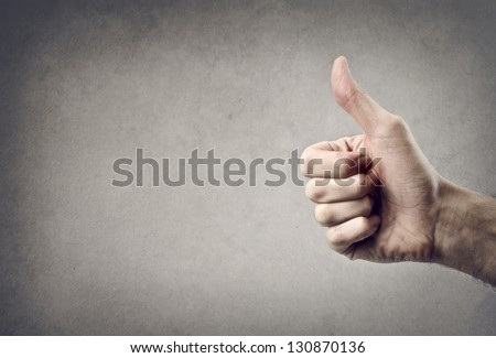 hand with thumb upwards on a gray background - stock photo