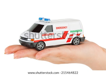 Hand with toy ambulance car isolated on white background - stock photo